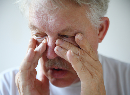 A senior man tries to relieve his stuffy nose.